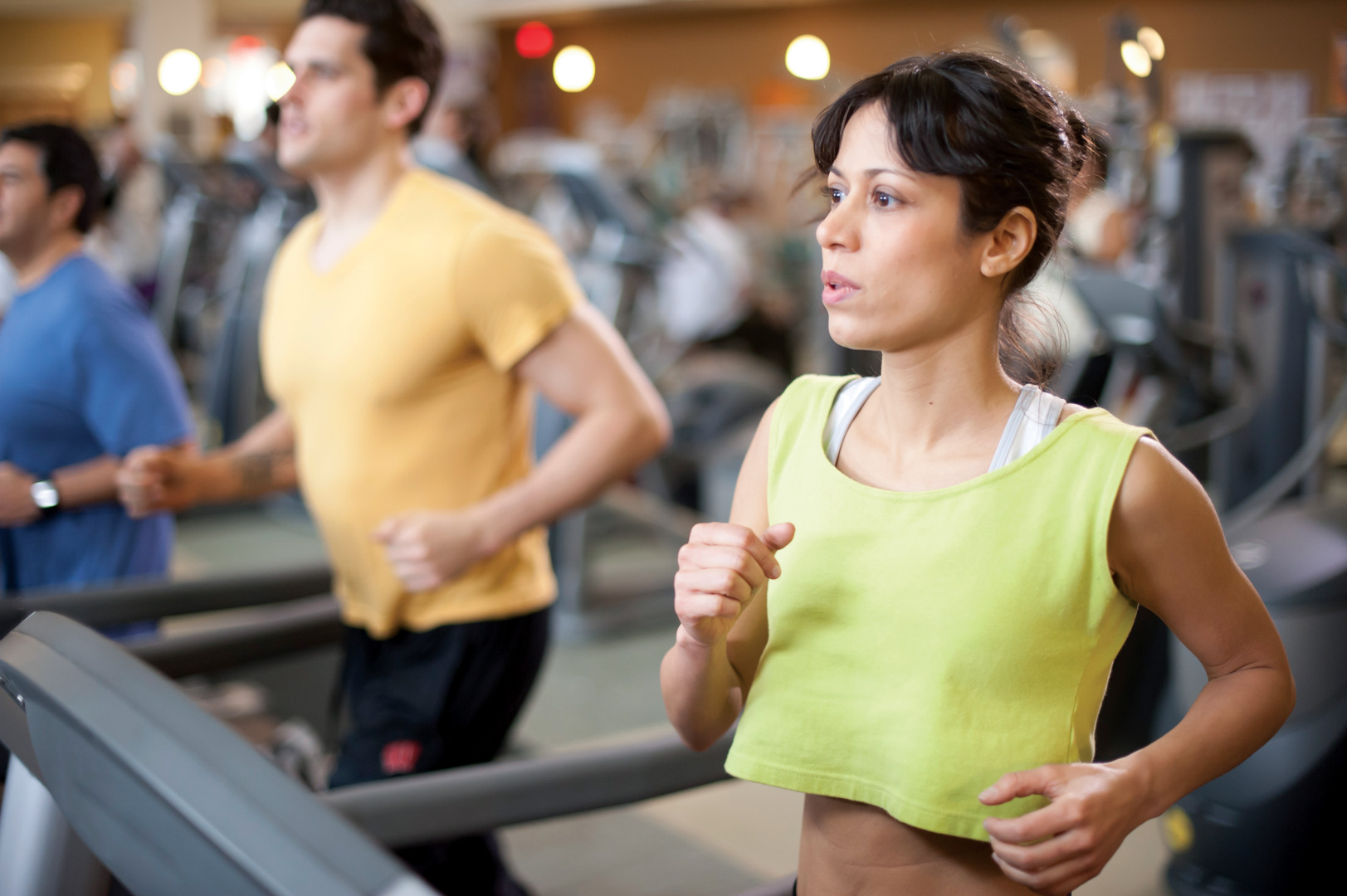 woman running on treadmill with man in background