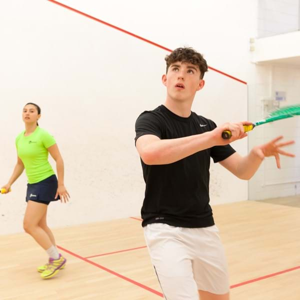 Young man and woman playing squash